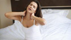 Siedząca kobieta na łóżku z bólem karku
